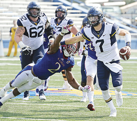West Virginia quarterback Will Grier (7) evades Kansas defensive end Dorance Armstrong Jr. (2) as he runs for a first down during the second half of an NCAA college football game in Lawrence, Kan. (AP Photo)
