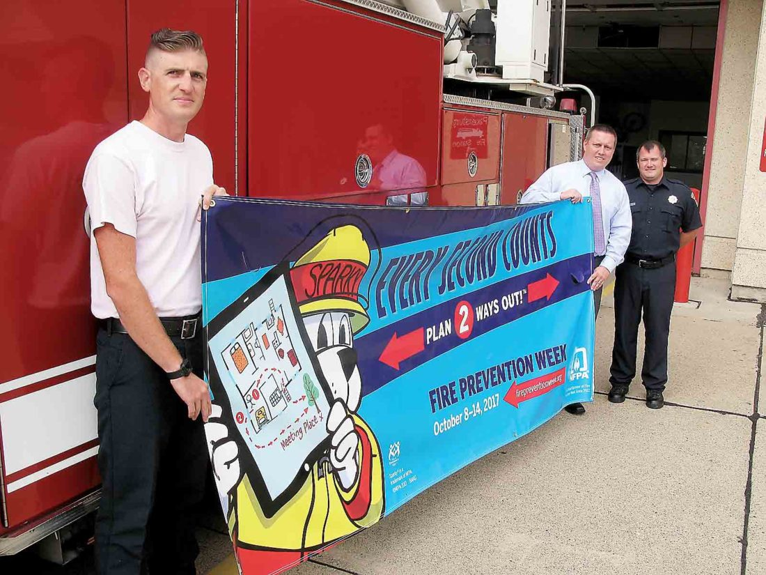 Photo by Jess Mancini From left Adam Delbaugh, Fire Chief Jason Matthews and Jeremiah Moyers of the Parkersburg Fire Department pose with a banner to be installed around town for the commemoration of National Fire Prevention Week, Oct. 8-14.