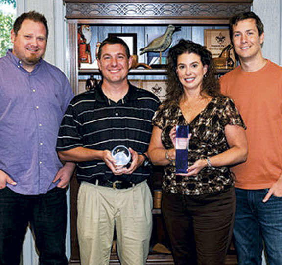 Photo Provided Woodcraft employees Kyle Crabtree, Jason Guthrie, September Fleming and Ryan Knost, from left, display the Avercast Crystal Ball Award and the WebLinc King of Content Award they received at national conferences recently.