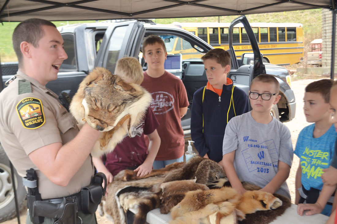 Photo by Michael Kelly Ohio Wildlife Officer Ryan Donnelly holds up a coyote pelt at the Schramm Farm on Friday as he teaches a group of Warren Local Schools students about wildlife and its relation to farming.