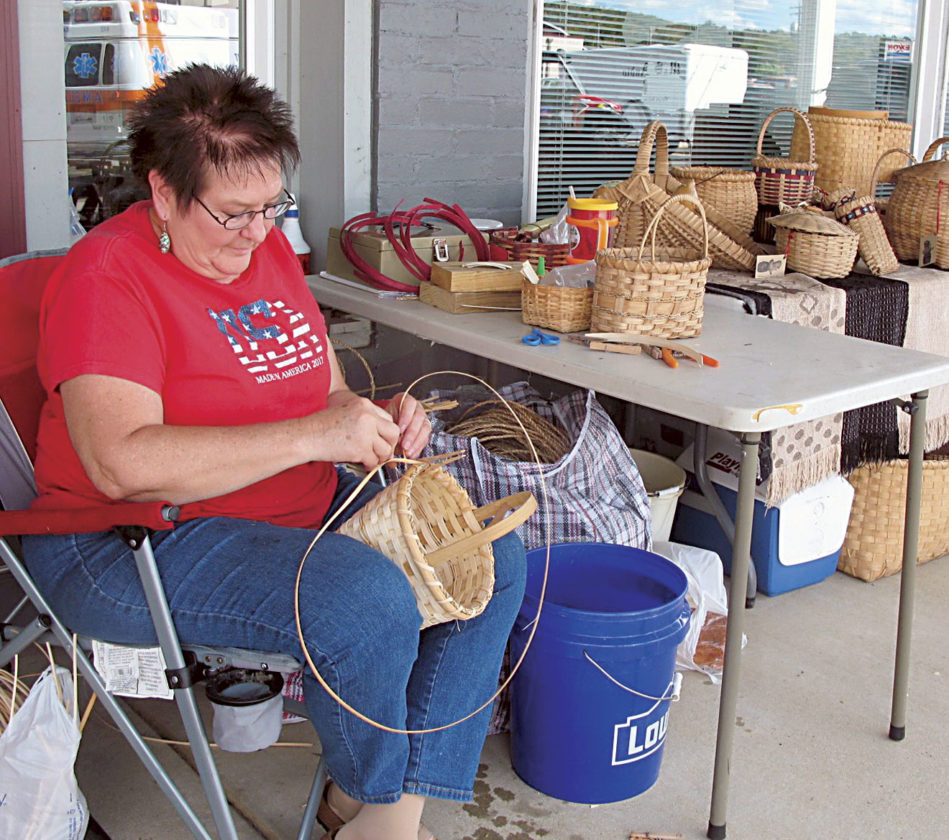 Photo by Jeffrey Saulton Wanda Wayne, of Roane County, shows her basket weaving during the Wirt County Pioneer Day in Elizabeth.