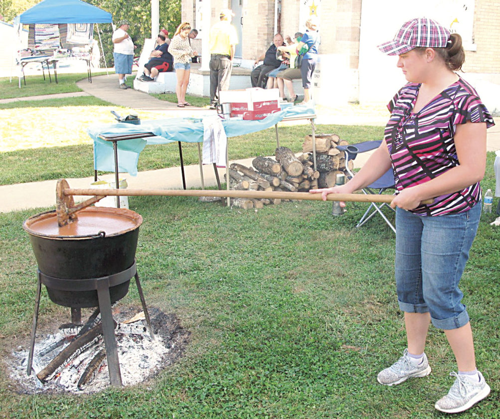 Photo by Jeffrey Saulton Karen Sims, of the Pisgah United Methodist Women, takes a turn at stirring apple butter at the Wirt County Pioneer Day in Elizabeth on Saturday.