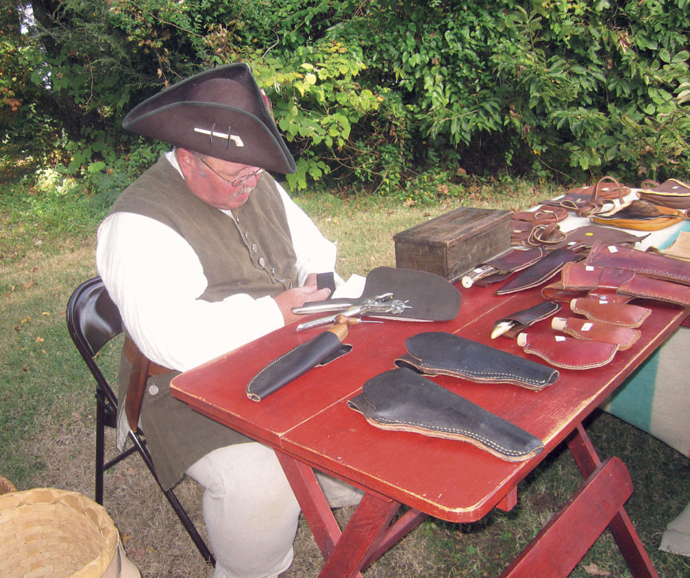Photo by Wayne Towner Doug Unsold, of Waterford, demonstrates leather working Saturday at the Farmers Castle Museum Education Center in Belpre.