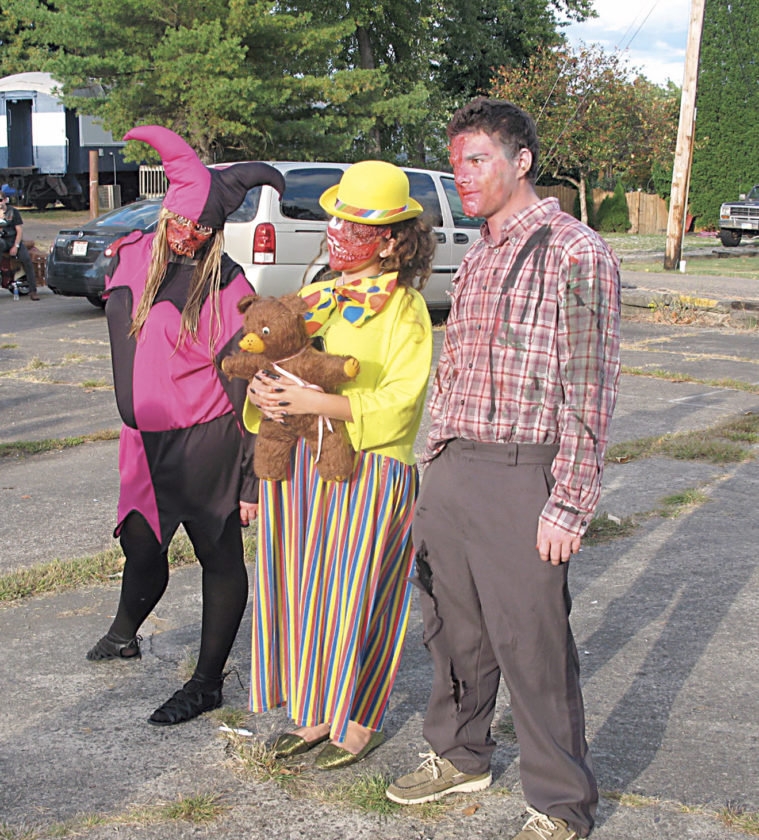 Photo by Jeffrey Saulton Sarah Dennis, left, of Marietta,  came to the Zombie Fest at Harmar Village on Saturday as a jester zombie and created the makeup for Lorena Cratsenburg's zombie clown, middle, and for Courtland Gibbs, right, as a zombie.