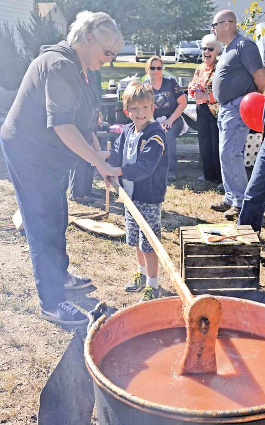 File Photo Bev Chapman, Pioneer Presbyterian Church, helps Corey Wiggins of Belpre stir apple butter Sunday during last year's Apple Butter Stir-Off at Howes Grove Park in Belpre. This year's event has moved to Civitan Park and will be held Saturday and Sunday.