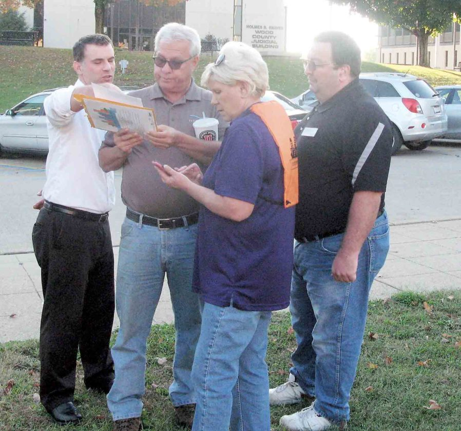 Photo by Jeffrey Saulton Parkersburg City Councilmen Eric Barber, John Reed, Sharon Kuhl and Bob Mercer as team Tax and Spend look over their clue sheet at the start of the Amazing Chamber Chase.
