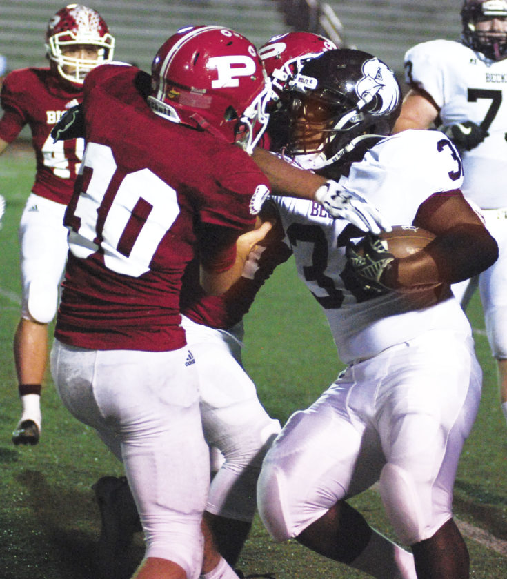 Photo by Jay W. Bennett Parkersburg's Brandon Braham joins in taking down Woodrow Wilson ball carrier LaMont Lee, Jr. during the Big Reds' 34-8 victory over the Flying Eagles last Friday. Braham and his teammate are back in the fire tonight with a trip to Cabell Midland.