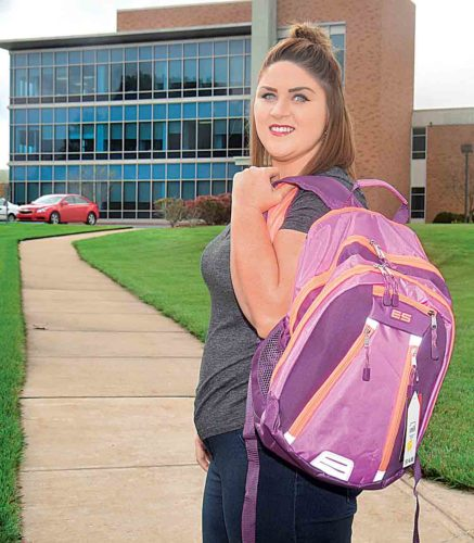 Photo by Jeff Baughan West Virginia University at Parkersburg student Emily Perdue holds a backpack which will be filled with items for foster care children in an eight-county region. The donation drive concludes Oct. 26 at the school's activity center.
