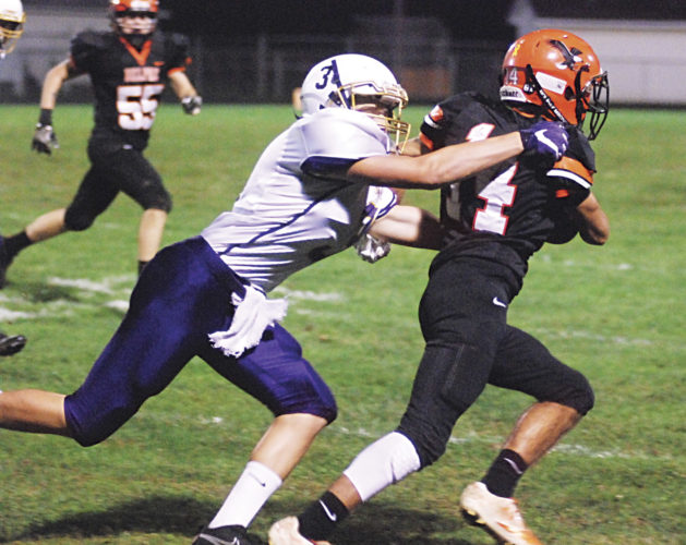 Photo by Steve Hemmelgarn Lucasville's Nate Crabtree (3) tries to tackle Belpre's Logan Adams (14) during Friday night's 48-7 Golden Eagles' loss.