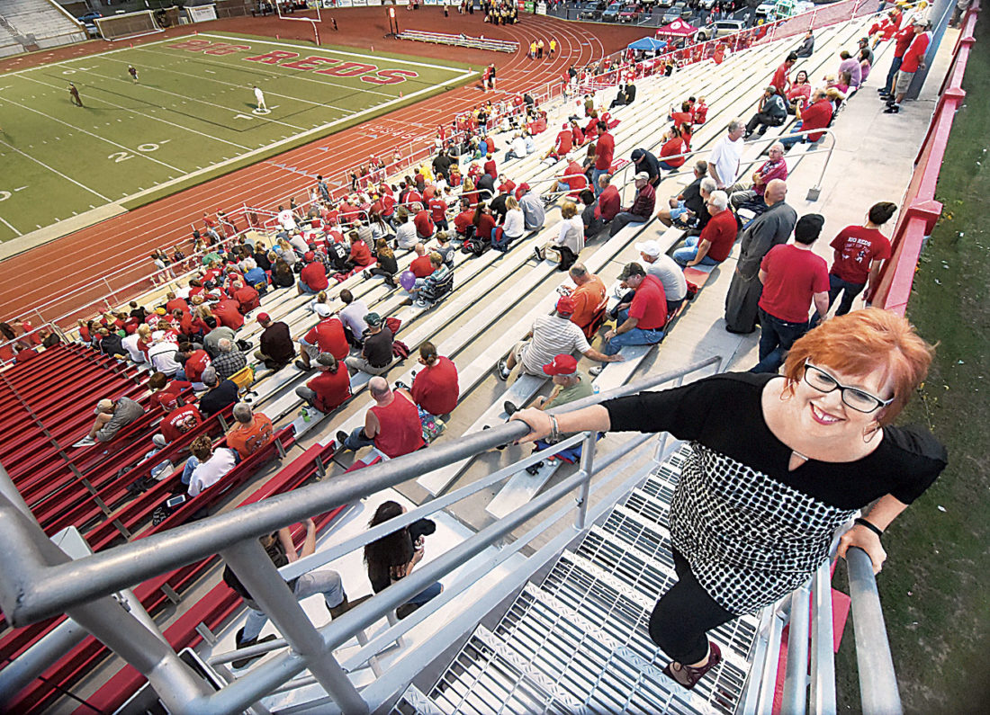 Photo by Jeff Baughan Lori Ullmann climbs the steps to the Stadium Field pressbox before the start of pregame preparation for the Woodrow Wilson-Parkersburg football game.