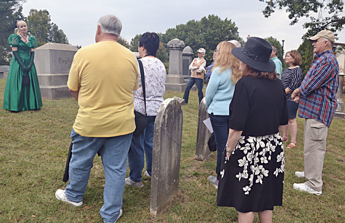 Photo by Brett Dunlap Julie Deklavon portrayed Clara Diss DeBarr, wife of artist Joseph H. Diss DeBarr who designed the great seal of the state of West Virginia. People toured the historical Riverview Cemetery on Juliana Street on Sunday as part of a dedication ceremony for a new fence surrounding the park.