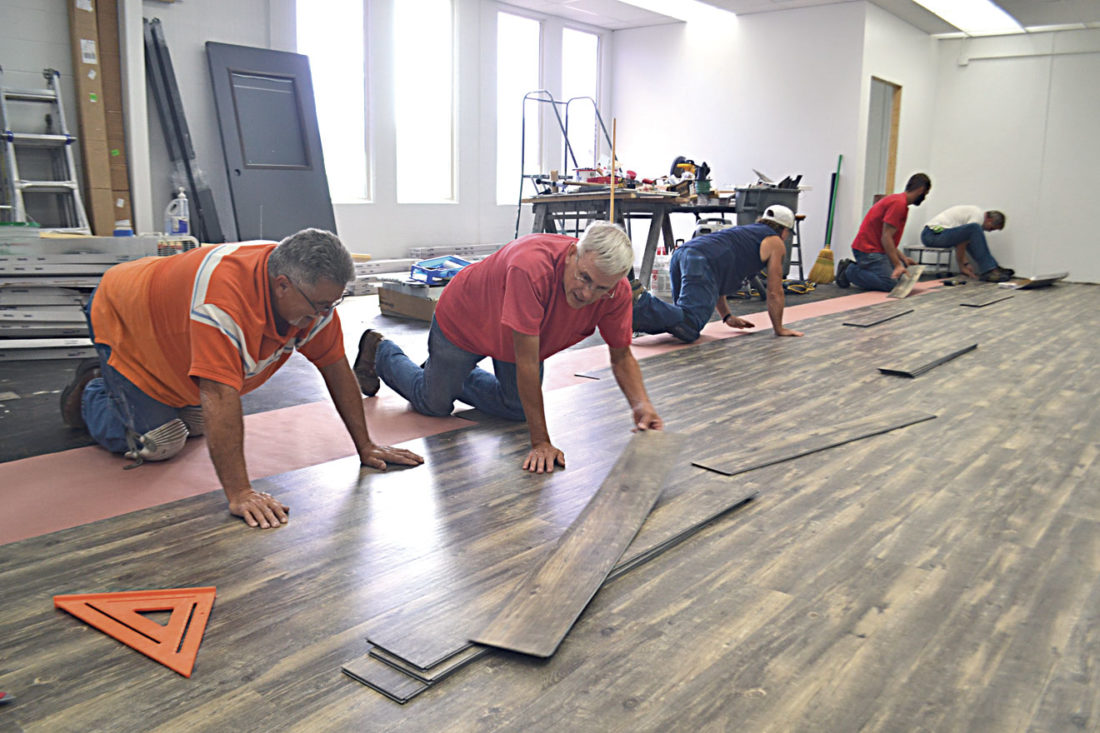 Photo by Michael Kelly Students in the Building Technology program lay flooring in one of the rooms at the Washington County Career Center on Thursday. The room eventually will become part of the center's heath instruction program. The Building Technology students last month did extensive renovations to the Disabled American Veterans Post No. 52 near Whipple.