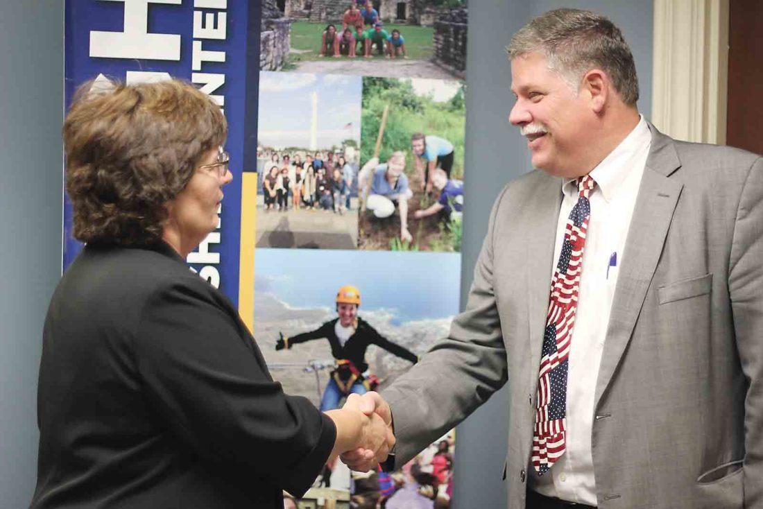 Marietta Municipal Court candidates Janet Dyar-Welch, left, and Paul Bertram, right, shake hands at the Marietta College McDonough Leadership Center after a debate Monday. (Photo by Janelle Patterson)