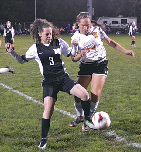 Massillon Washington's Deja Benjamin, left, battles Marietta's Ava Limegrover, right, for the ball during girls' soccer sectional tournament action at Jerry Brock Field Monday night. The Marietta Tigers won 6-2. Photo by Ron Johnston.
