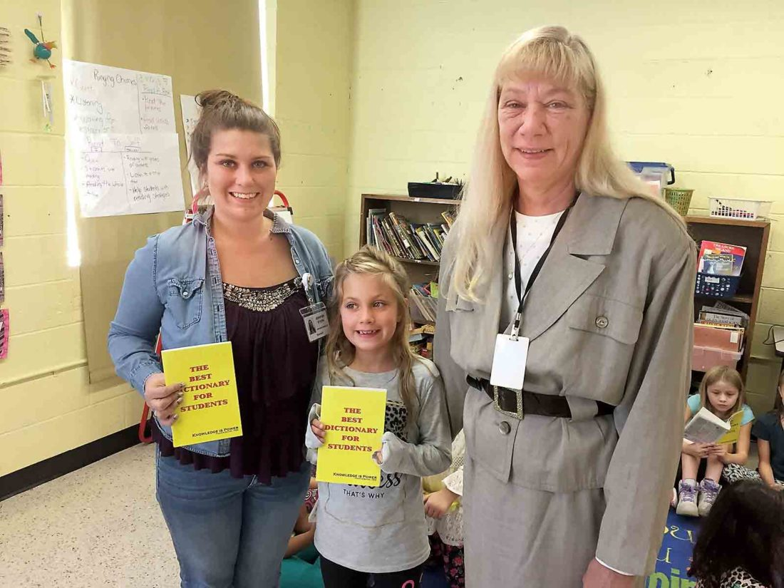 "Photo Provided Fairplains Elementary School teacher Jennifer Byers, left, along with her daughter and third-grader Laiken Byers, center, hold up copies of ""The Best Dictionary for Students,"" donated to all Wood County third-graders by Sherry Dugan, right, and other members of the Parkersburg Elks 198. The organization donated more than 900 dictionaries to area schools."