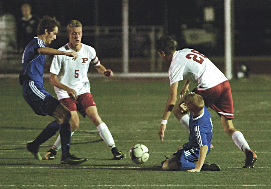 Ripley teammates  Elijah Ross (14) and Keagun Jackson (1) along with Parkersburg's Ian Domenick (5) and Anthony Fleshman (26) scramble for a loose ball during the Big Reds' 3-1 Class AAA Region IV, Section 1 victory over the Vikings Tuesday night. Photo by Joe Albright.