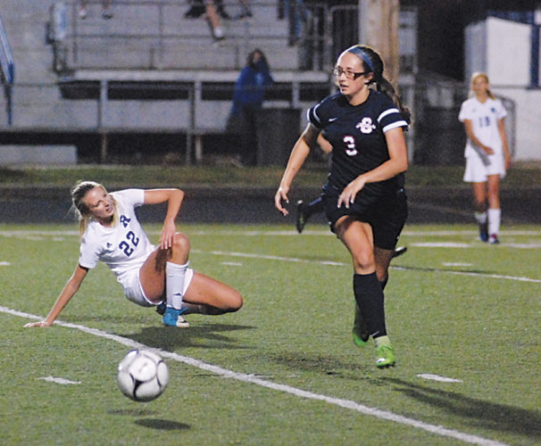 Parkersburg South's Callie Leasure passes the ball while Ripley's Cassidy Miller tries to regain her footing during a high school soccer match Wednesday in Ripley. Photo by Steve Hemmelgarn.