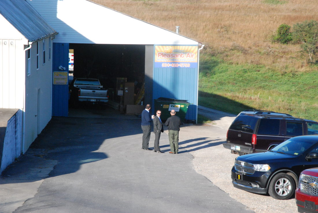 Photo by Evan Bevins From left, Wood County Assistant Prosecutor Russell Skogstad, Prosecutor Pat Lefebure and Sheriff Steve Stephens confer this morning at Pleasants Air at 5200 Emerson Ave., where the body of a white male was discovered. Stephens said the death is suspicious.