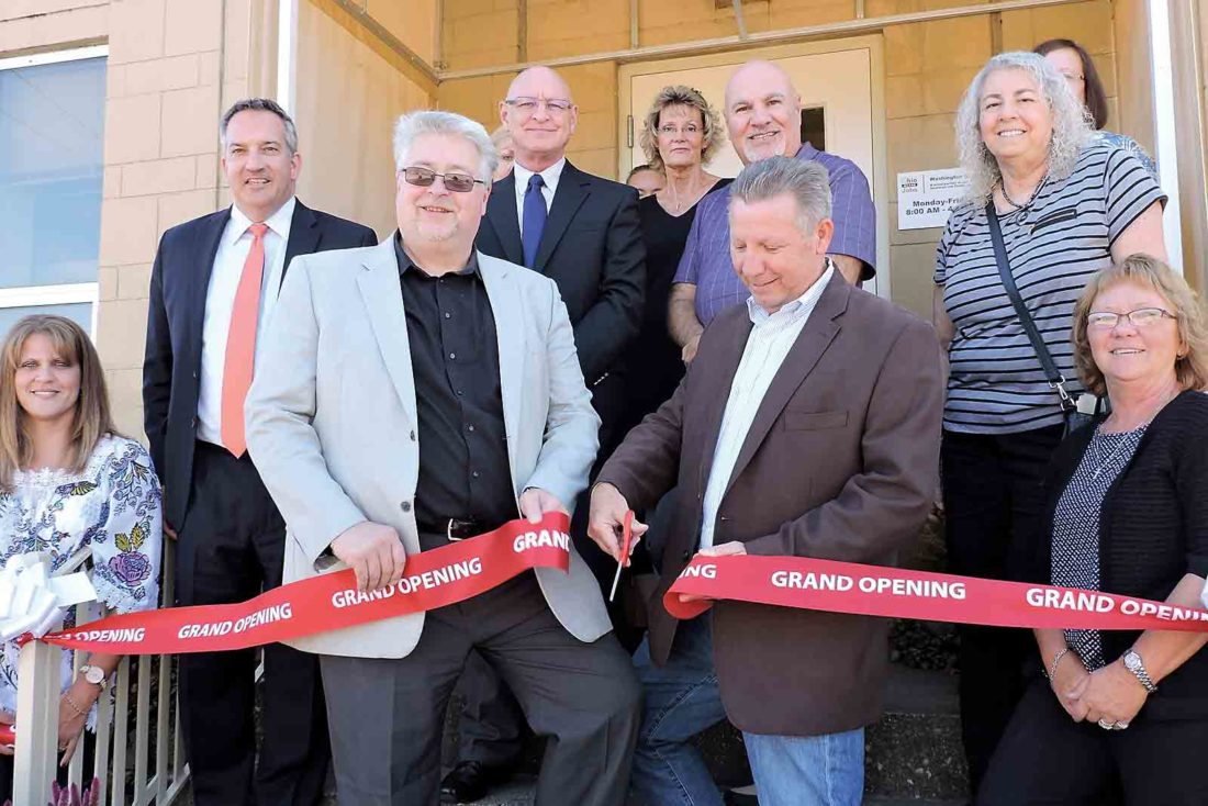 Photo by Sam Shawver Washington County Commissioners Ron Feathers, left, and Rick Walters cut the ribbon at the entrance to the OhioMeansJobs Center during an open house at the center on Friday.