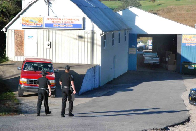 Photo by Evan Bevins Wood County Sheriff's deputies walk down the driveway to Pleasant Air at 5200 Emerson Ave. just north of Parkersburg while investigating a homicide Friday morning. Employees of the business discovered the body of a white male there around 7:30 a.m.