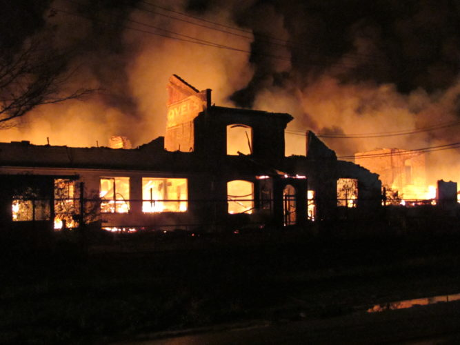 Photo by Jess Mancini. A wall is back lit by the inferno at the former Ames shovel plant in south Parkersburg.