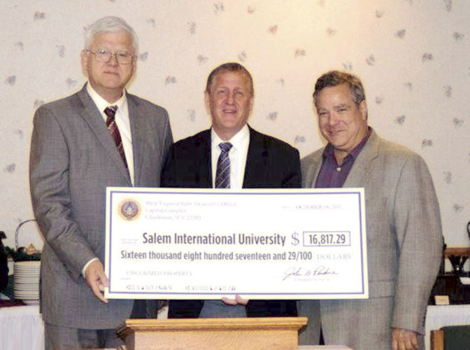 Photo Provided From left, state Treasurer John Perdue, Salem International University President Danny Finuf and state Sen. Mike Romano, D-Harrison, pose with a check for $16,817 given to the college from unclaimed property administered by the state treasurer's office.