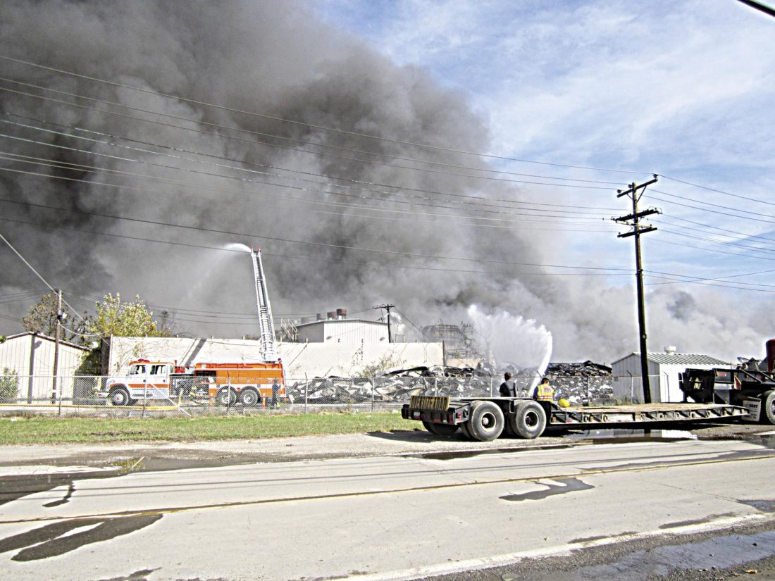 Photo by Wayne Towner Efforts to fully extinguish the fire and suppress the smoke rising into the air at the old Ames Plant in south Parkersburg are expected to take several days. Officials are continuing to look for ways to address the fire and begin cleanup operations.