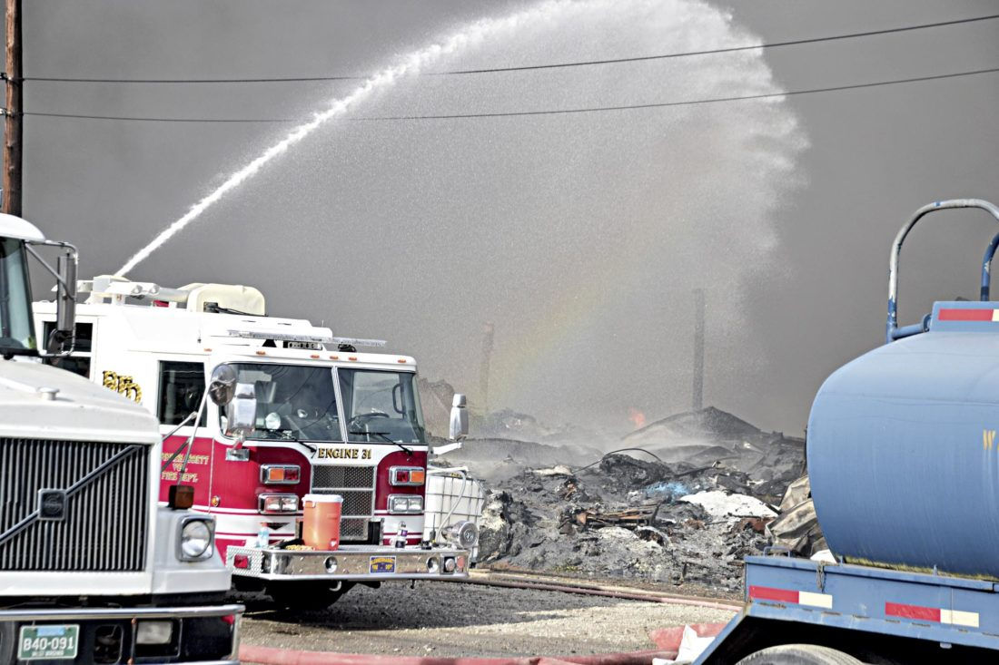 Photo by Brett Dunlap Local fire crews continued Sunday to fight the fire at the old Ames Plant in south Parkersburg.