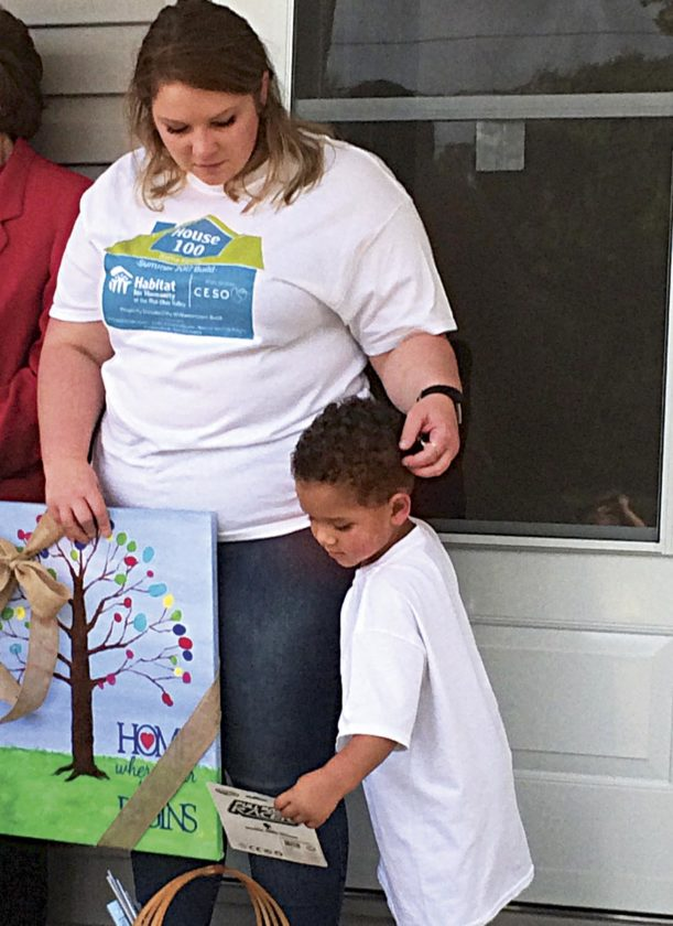 Photo by Brett Dunlap Ashley Sams and her son Jissai received a painting from the Williamstown Public Library and a basket of books from Alpha Delta Kappa during the dedication of the 100th home built locally by Habitat For Humanity.