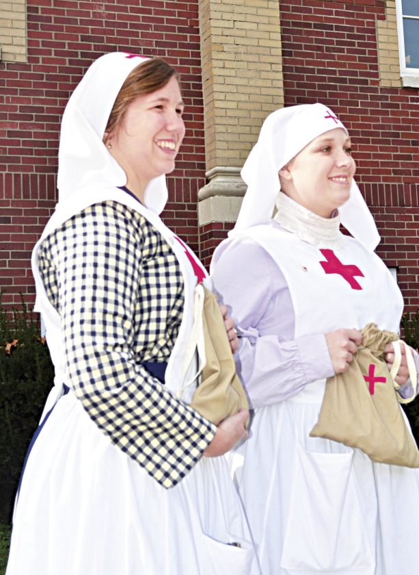 Photo by Doug Loyer Jessica Cyders and Teghan Sharp, of the Southeastern Ohio History Center, hold comfort kits that the American Red Cross would have made 100 years ago.