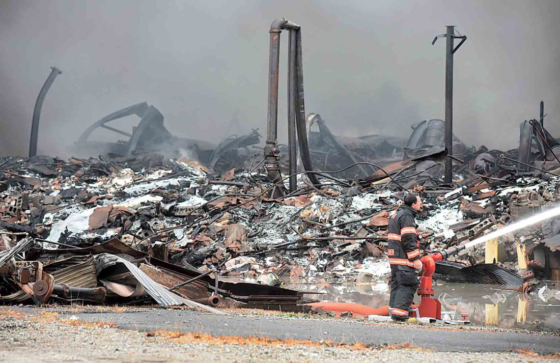 Smoke rises Tuesday from the smoldering remains of the IEI Plastics fire at a warehouse on Camden Avenue.