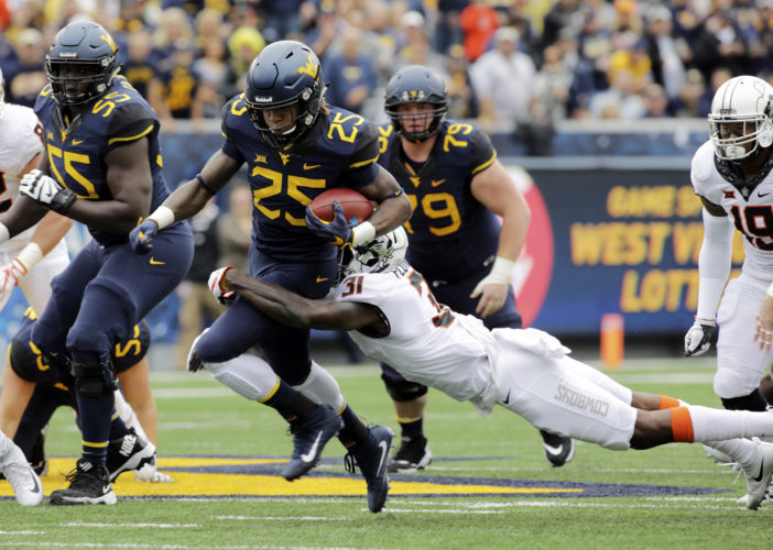 West Virginia running back Justin Crawford (25) is tackled by Oklahoma State safety Tre Flowers (31) during the first half of an NCAA college football game, Saturday, Oct. 28, 2017, in Morgantown, W.Va. (AP Photo/Raymond Thompson)