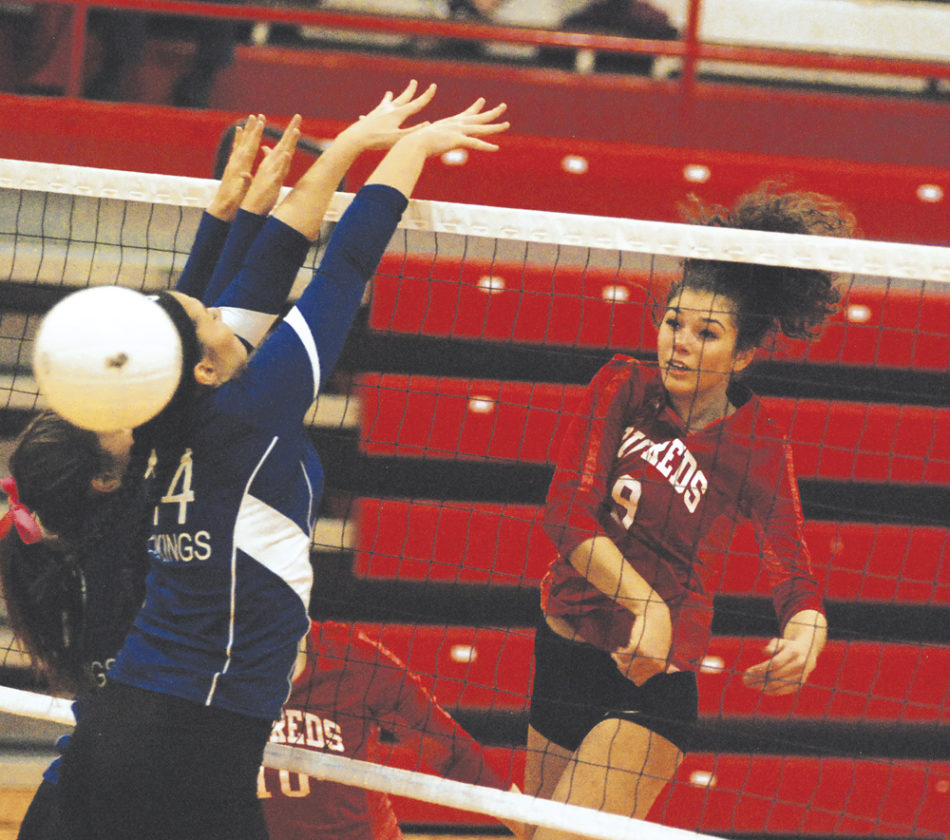 Parkersburg High School's Shay-Lee Kirby powers a spike past the double block of Ripley's Kenzie Casto (14) and Anna Kurnot (9) during Wednesday's Class AAA sectional tournament inside Memorial Fieldhouse. PHS claimed the sectional title, but both the Big Reds and Vikings will return for the regional on Saturday morning. Photo by Jay W. Bennett.