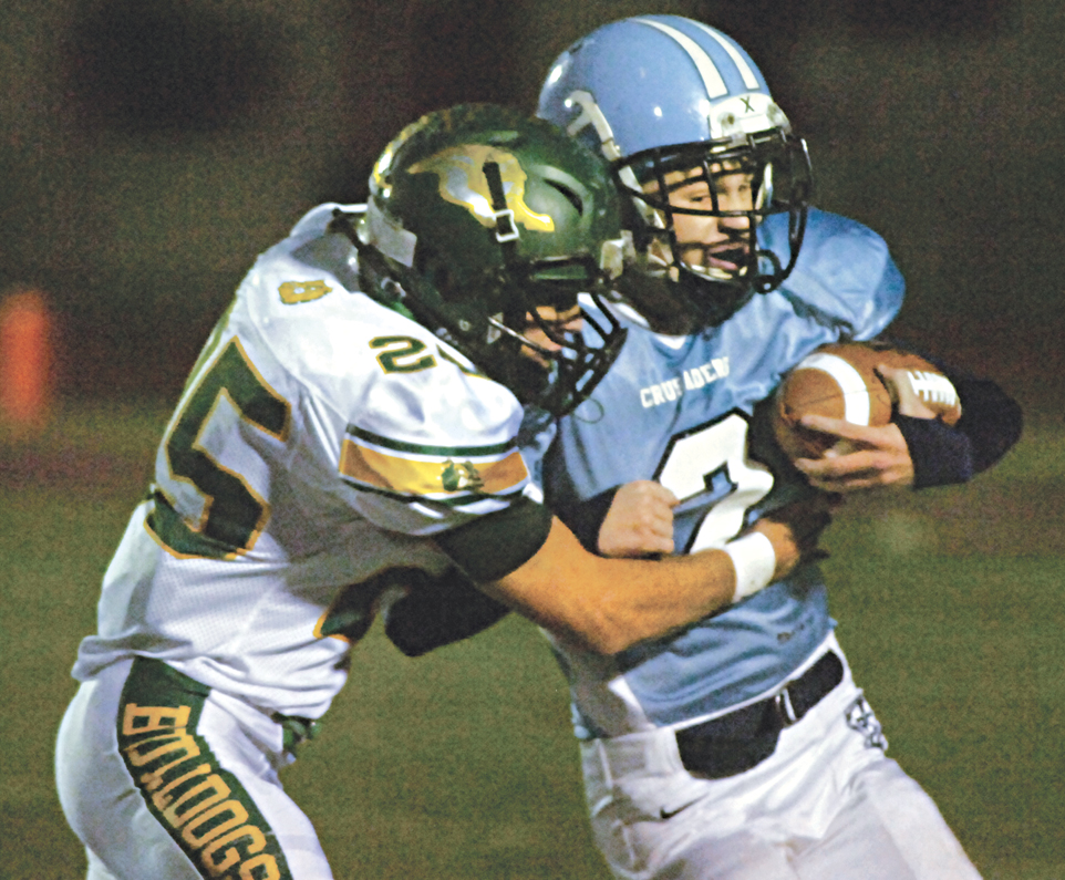 Doddridge County's Carson Montgomery wraps up Parkersburg Catholic's Nick Stricker, while he runs the football, during the Bulldogs' 67-6 win over the Crusaders Friday night at PHS Stadium Field. Photo by Joe Albright.