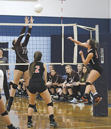 Wirt County's Taylor Anderson spikes the ball over the block of Williamstown's Skyler Chancellor during Thursday's Class A sectional final at Parkersburg Catholic. Both the Tigers and Yellowjackets will play this afternoon in Elizabeth with berths to next week's state volleyball tournament on the line. Photo by Michael Uhl.