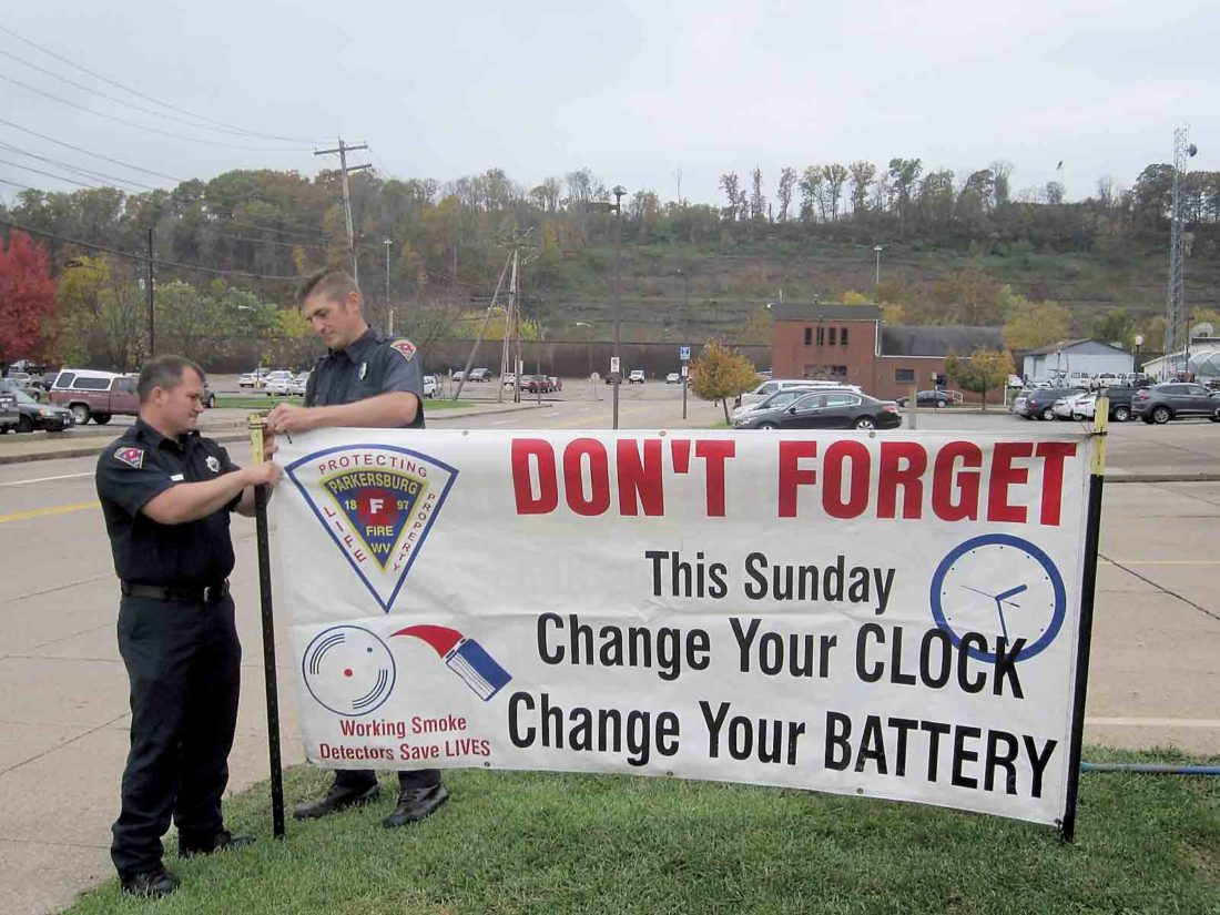 Photo by Wayne Towner Firefighters Jeremiah Moyers, left, and Adam Delbaugh, right, put up a banner in front of Parkersburg Fire Station 1 on Friday at the Parkersburg Municipal Building. Officials are urging residents to check the batteries in their smoke and carbon monoxide detectors this weekend with the ending of daylight-saving time early Sunday morning.