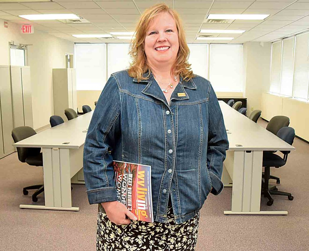 Photo by Jeff Baughan Chamber of Commerce of the Mid-Ohio Valley President/CEO Jill Parsons stands in front of the tables and chairs which are part of a new training center being established in the chamber's offices in the United Building.