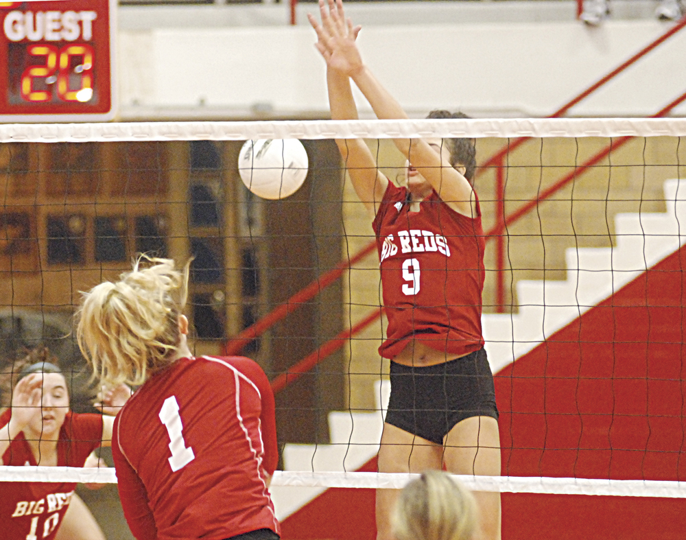 Parkersburg High's Shay-Lee Kirby (9) leaps to attempt to block a ball hit by Hurricane's Brianna Washburn (1) during a Class AAA, Region IV volleyball semifinal Saturday at PHS Memorial Fieldhouse. The host Big Reds bowed out of tournament play with a 25-21, 27-25, 25-23 setback at the hands of the Redskins. Photo by Steve Hemmelgarn.