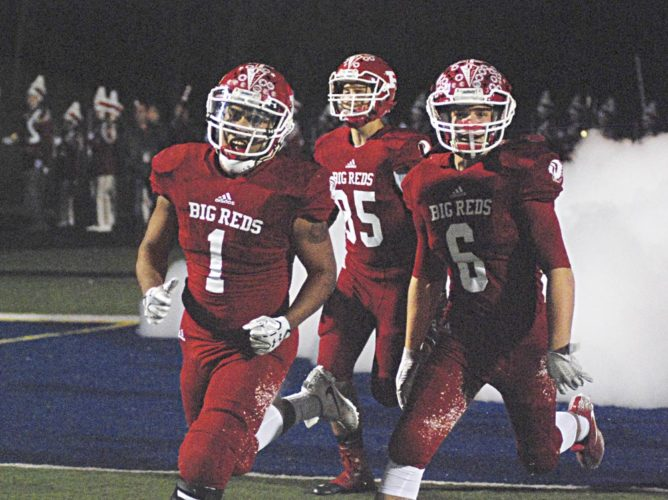 Parkersburg Big Reds Zion Atkinson (1), Caden Florence (6) and Nathaniel Steed (85) run onto the field during a high school football game earlier this season against Riverside.