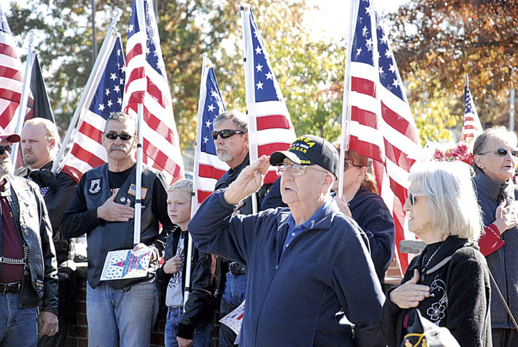 "File Photo Korean War Army veteran Orville Allen, front left, of Parkersburg, salutes as combined high school bands play ""The Star-Spangled Banner"" during last year's Veterans Day program at City Park in Parkersburg. Standing beside Allen was Parkersburg resident Linda Hatfield, sister to seven brothers who served in the military."