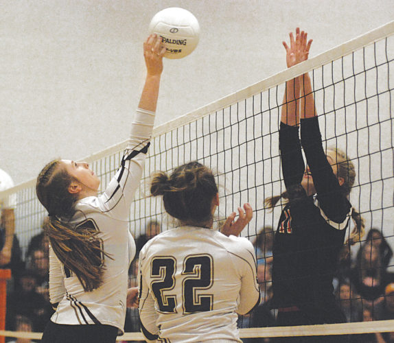 Williamstown's Kayla Bauman, left, tries to tip the ball past the block of Wirt County's Emma Wyer during Class A regional action last Saturday in Elizabeth. The Yellowjackets of head coach Rachelle Cole square off against Ritchie County at 8:30 a.m. Friday in the state quarterfinals inside the Charleston Civic Center. Photo by Jay W. Bennett.