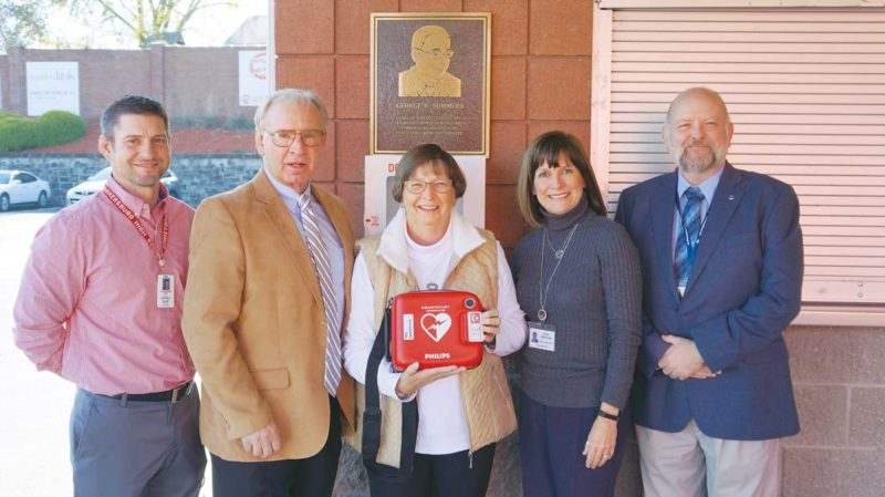 Photo by Michael Erb Parkersburg High School Athletic Director Chris Way, left, Wood County Schools Superintendent John Flint, center left, retired teacher Monica Davis, center, Health Services Coordinator Julie Bertram, center right, and Safety Coordinator Don Brown, right, stand with a new AED unit which will be available during activities at PHS Stadium Field. Two AED units have been installed at each of the district's high school stadiums.