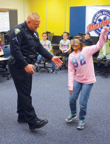 Photo by Michael Erb Parkersburg South High School Prevention Resource Officer Todd Lambiotte reaches out to steady Mineral Wells Elementary School fourth-grader Natalie Alderman as she struggles to perform a balance test while wearing goggles that simulate intoxication.