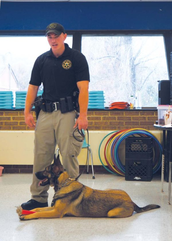 Photo by Michael Erb Wood County Sheriff's Deputy Jeff Kidder stands with Maggi, a female German shepherd, Thursday while speaking to students at Mineral Wells Elementary School as part of the annual drug awareness day program.