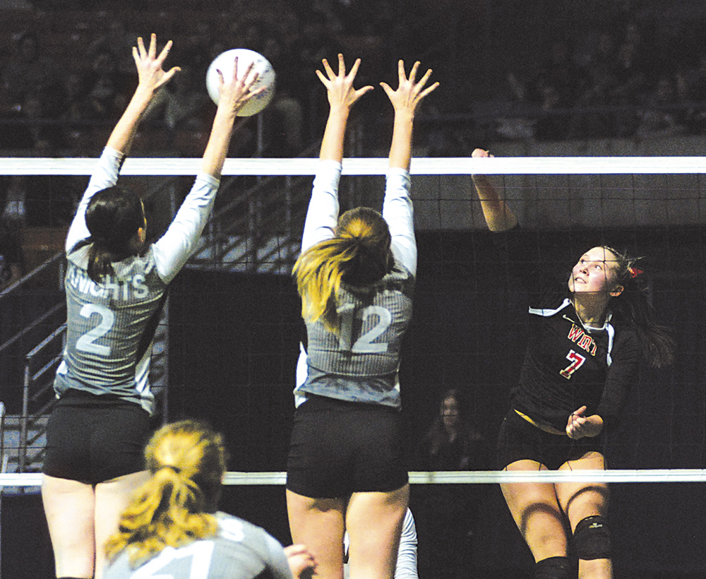 Wirt County's Haley Moore (7) spikes ball as Tyler Consolidated's Emily Lancaster (2) and JoLee Walton (12) try to block it during a state volleyball match Friday in Charleston.  Photo by Jay W. Bennett.