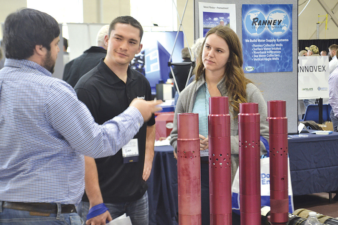 Photo by Michael Kelly Attendees talk to a company representative with a perforated pipe sample at the first Marietta College Oil & Gas Technical Exhibition held Friday at the Dyson Baudo Recreation Center on the college campus.