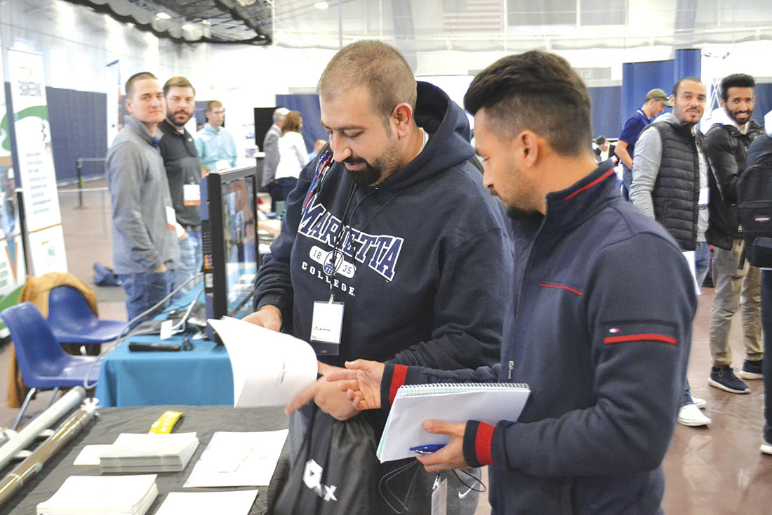 Photo by Michael Kelly Two petroleum engineering students from Marietta College look at literature from a company at the first Marietta College Oil & Gas Technical Exhibition held Friday at the Dyson Baudo Recreation Center on the college campus.