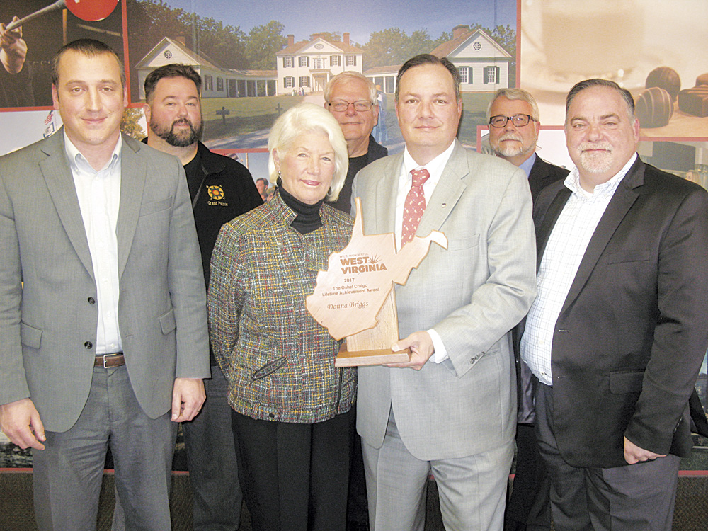 Photo by Jess Mancini Front row, Greater Parkersburg Convention and Visitors Bureau Vice Chairman Michael Gibson, left, Bureau Chairman Blair Couch, third from left, and immediate past Chairman Alan Hardway, right, present Donna Briggs with the Oshel Craigo Lifetime Achievement Award on Thursday. Back row, from left, bureau Treasurer Chad Winebrenner, Secretary Cal Malcom and President and CEO Mark Lewis.