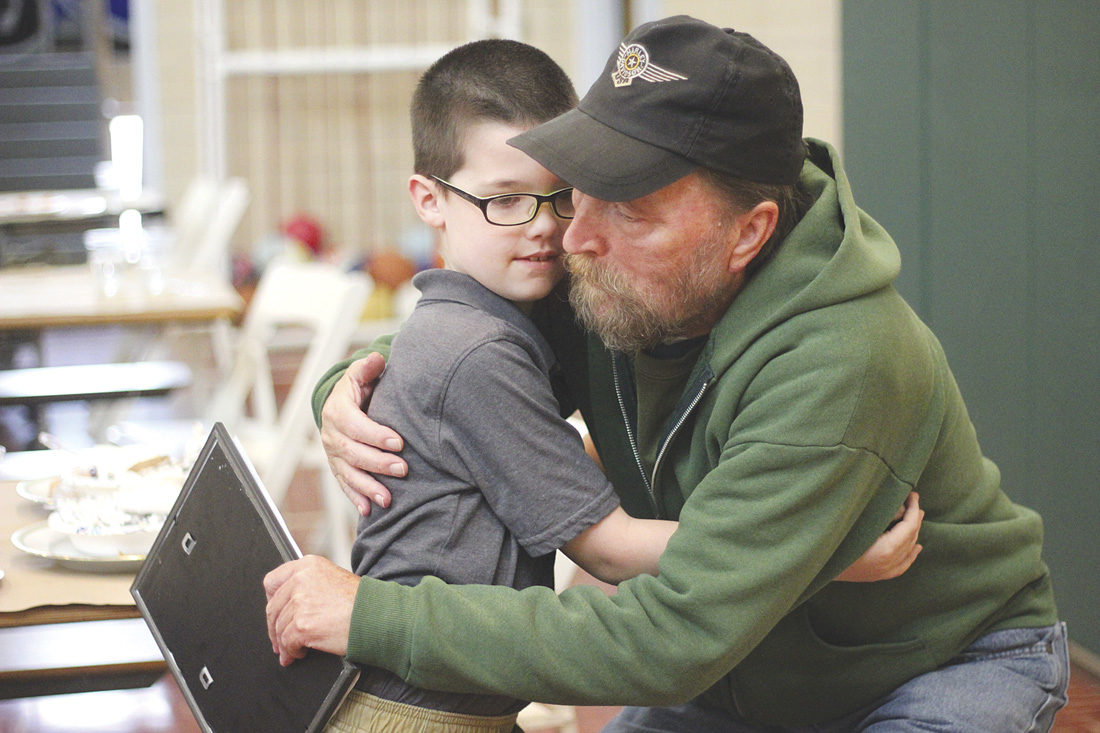 Photo by Janelle Patterson Roger Watkins, 65, a U.S. Navy veteran from Belpre, takes a hug from his grandson Christopher Watkins, 7, at the veterans appreciation luncheon at Veritas Classical Academy Friday.