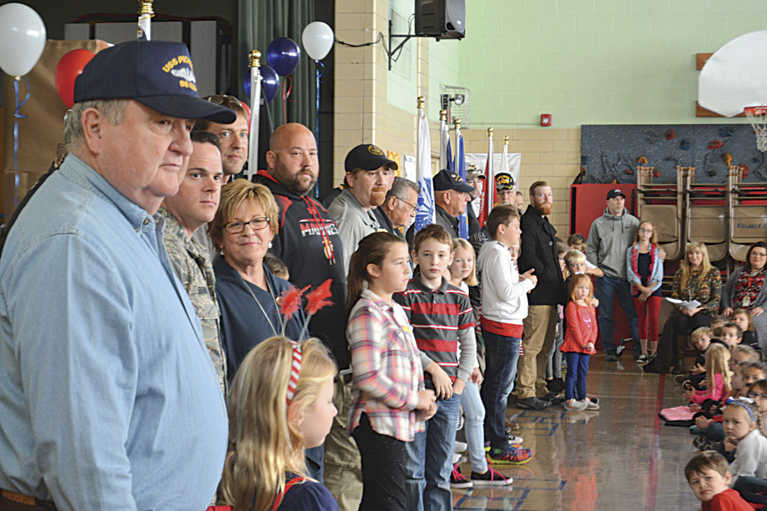 Photo by Michael Kelly Veterans stand with students at Harmar Elementary School. Many have been coming to the annual tribute put on by the school for Veterans Day for several years, and many had children or grandchildren who participated in the event.